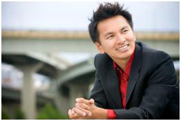 Homme de type asiatique souriant, vêtu d'un costume noir sur une chemise rouge.