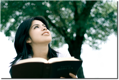 woman looking into the distance while holding a Bible