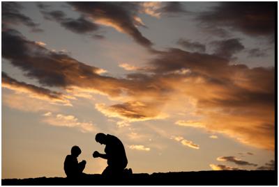 man och barn på knä i bön