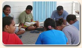 ekklesia de maison, groupe de maison; église au foyer; des adultes et des enfants réunis pour le service de culte, adoration, étude biblique, chant d'hymnes; personnes assises sur une terrasse en bois, porte bleue aux murs blancs, ayant un livre, une Bible à la main ou sur les genoux.