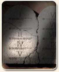 Les Dix Commandements; deux tablettes de pierre; les tables de la loi divine, fissurées, avec des chiffres romains, cinq de chaque côté; dans l'ombre; le quatrième commandement du Sabbat du septième jour éclairé, illuminé