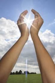 deux mains levées au ciel, jointes par leur base et les doigts légèrement écartés, pour laisser passer le rayonnement du soleil en leur milieu, sur un fond de ciel supérieur bleu et inférieur avec nuages blanc et gris, au dessus d'une prairie verte.