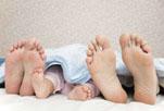 sommeil – pieds d'un couple et d'un bébé sous une couverture, vus de dessous